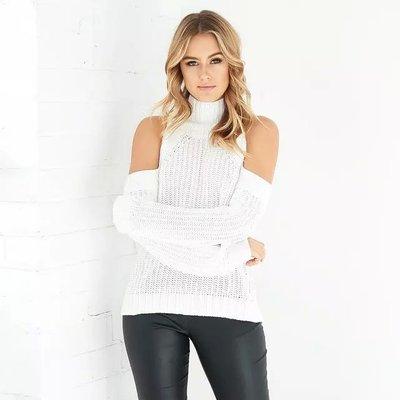 Modelo usa calça preta corino, blusa de lã branca com ombros vazados.