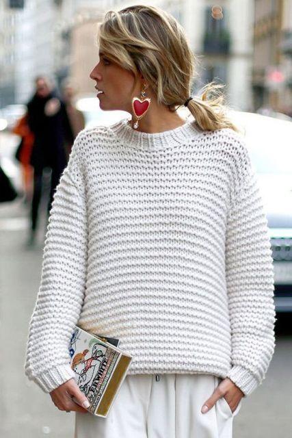 Modelo usa blusa de lã branca, saia branca e bolsa clutch.