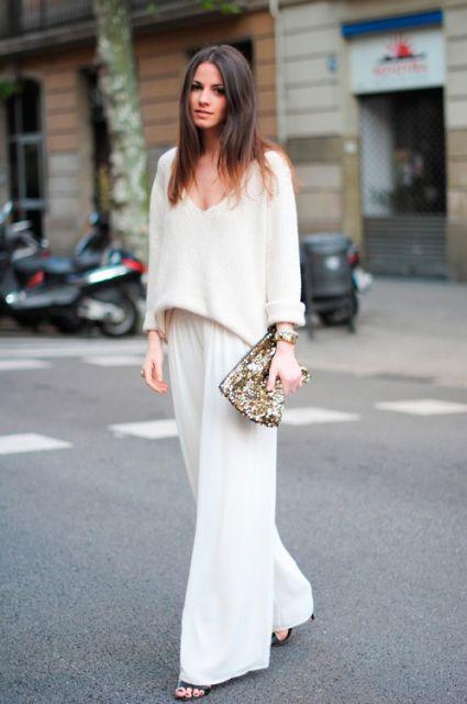 Modelo veste calça pantalona branca e blusa de lã branca.