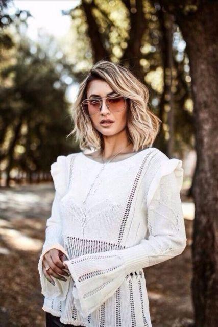 Modelo usa blusa de lã com manga flare na cor branca.