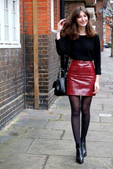Modelo usa saia vermelha vinil, sapato preto, meia preta transparente, blusa de lã preta e bolsa preta.