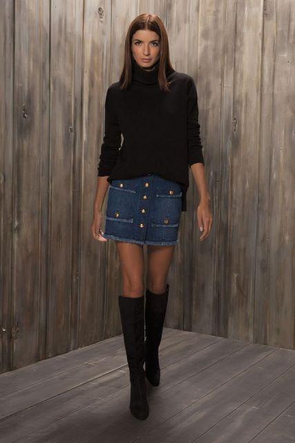 Modelo veste saia de botões jeans, bota preta cano longo e blusa preta de gola.