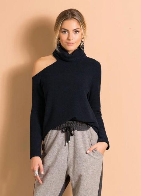 Modelo veste calça de moletom cinza e blusa de lã preta.