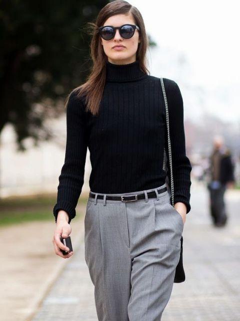 Modelo veste blusa preta gola alta de lã com calça social cinza.