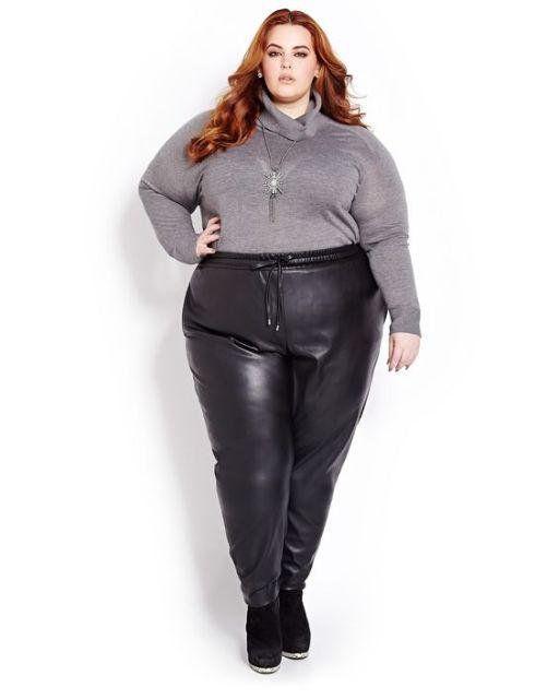 Modelo veste calça preta corino com blusa de lã cinza gola alta.