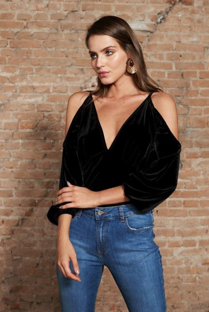 Modelo usa blusa preta ombros vazados de veludo e calça jeans azul.