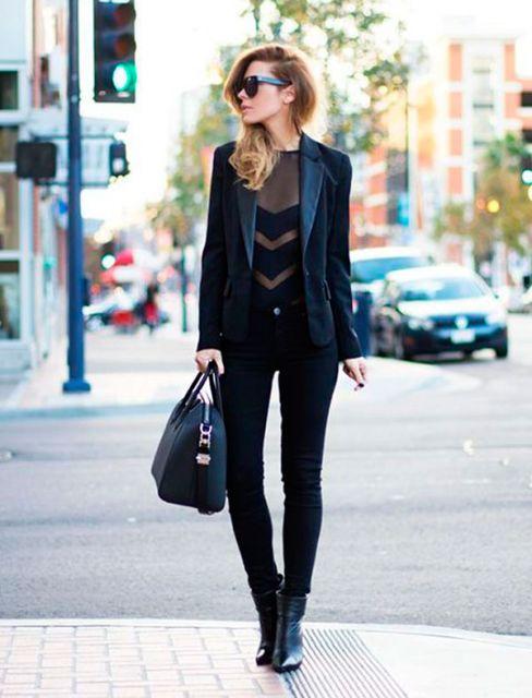 Modelo usa calça preta, body transparente, blazer e bolsa preta.