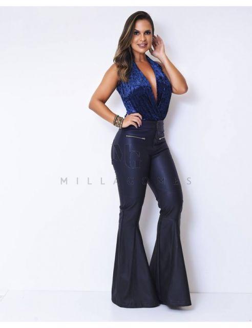 Modelo veste calça preta flare e body azul em veludo molhado.