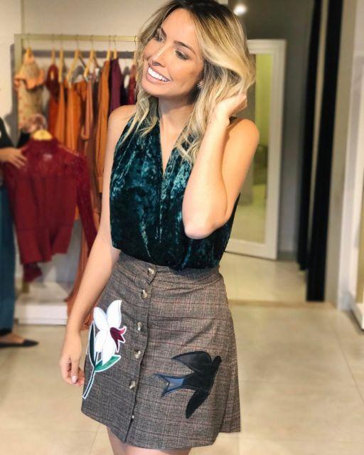 Modelo usa saia cintura alta de botão com blusa de veludo verde.
