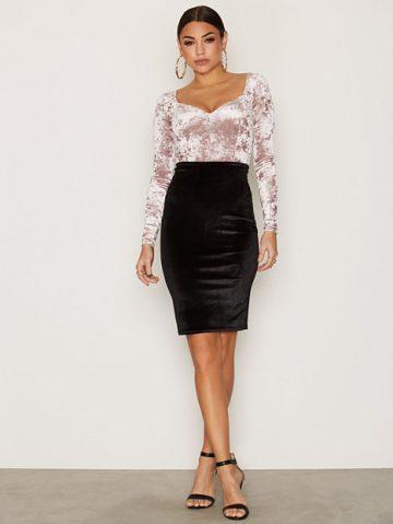 Modelo usa saia preta, body rosa claro e sandalia preta.