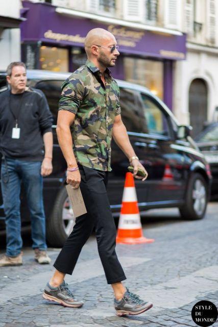 Homem caminhando na rua enquanto segura um envelope em uma mão e o celular na outra. Ele veste uma camisa camuflada masculina da manga curta acompanha de calça preta e tênis esportivos.