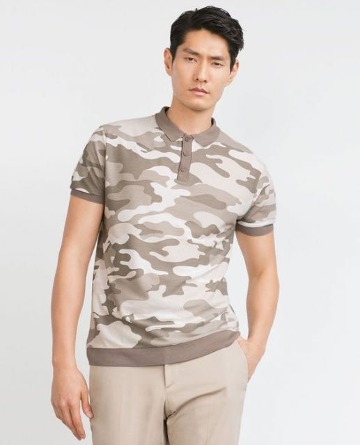 Homem em fundo branco vestindo uma camisa camuflada masculina de mangas curtas em tons arenosos.