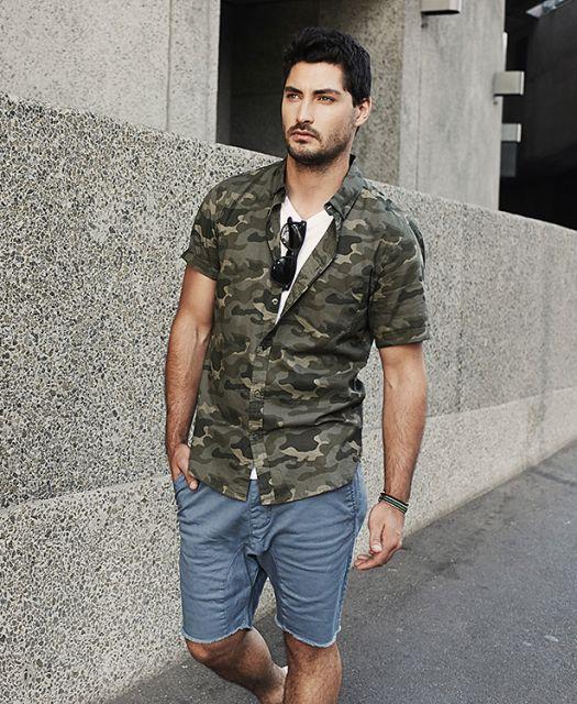 Homem caminhando na rua vestindo uma bermuda e camisa camuflada masculina de mangas curtas desabotoada nos botões próximos ao pescoço, onde carrega um óculo de sol.