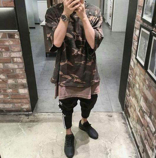 Homem tirando selfie no espelho vestindo uma camiseta camuflada long line acompanhada de uma calça da adidas.