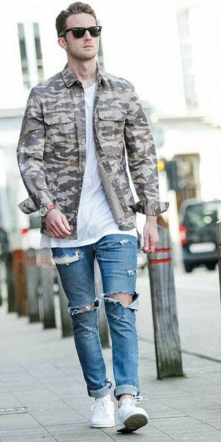 Homem caminhando na rua vestindo uma camisa camuflada aberta com dois bolsos frontais na região do peito.  Ele também usa óculos escuros e uma calça jeans rasgada.