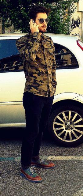 Homem falando ao celular em frente a um carro. Ele veste camisa camuflada de manga longa com dois bolsos frontais abotoada até o pescoço.