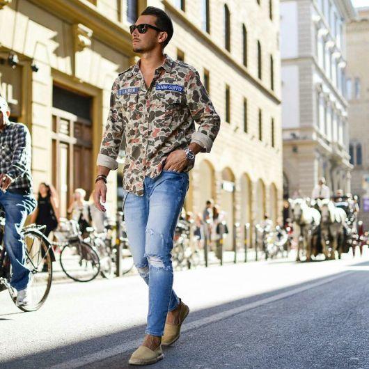 Homem de óculos escuros caminhando na rua com a mão no bolso. Ele veste camuflada masculina da manga dobrada, calça jeans rasgada no joelho e alpargatas.