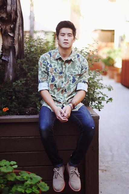 Homem sentado ao lado de uma árvore vestindo uma camisa camuflada com dois bolsos frontais abotoada e com as mangas dobradas na altura do cotovelo.