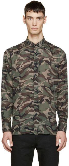 Homem vestindo camisa camuflada masculina abotoada até o pescoço com manga longa e sem nenhuma detalhe adicional além da estampa de camuflagem.