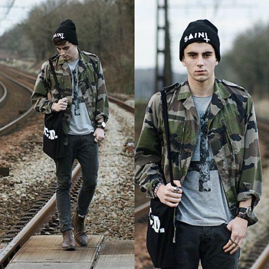 Duas fotos do mesmo homem caminhando nos trilhos de um trem. Ele veste uma camisa camuflada masculina aberta com botas, gorro e calça jeans.