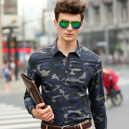 Homem de óculos escuros espelhado caminhando na rua com o fundo desfocado. Ele segura uma pasta com uma mão e veste uma camisa camuflada masculina de manga longa abotoada até o penúltimo botão.
