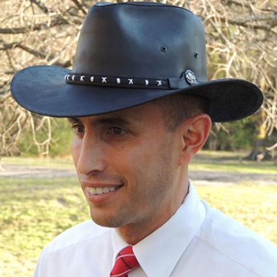 Homem com chapéu de couro preto e trajes sociais visto lateralmente.