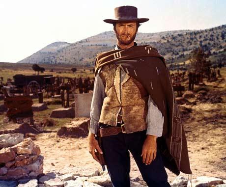 Clint Eastwood como O Homem Sem Nome vestindo um colete com um pano por cima. Ele usa um chapéu de couro desgastado.