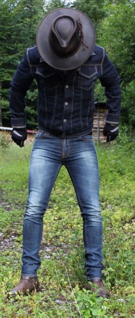 Homem em uma paisagem natural olhando para baixo. Seu chapéu é preto e de couro com a lateral plana.