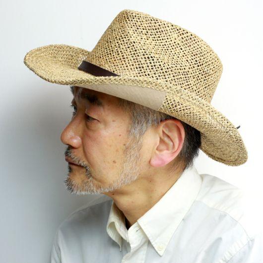 Homem idoso oriental de perfil usando um chapéu country de palha.