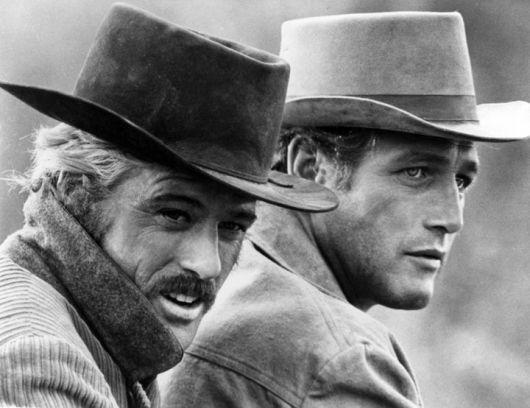 Paul Newman e Robert Redford usando trajes típicos de cowboys americanos, inclusive o chapéu.