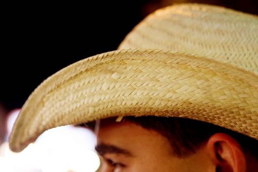 Foto com foco em um chapéu de palha na cabeça de um homem. A palha é bem entrelaça para não deixar espaços em branco no chapéu.