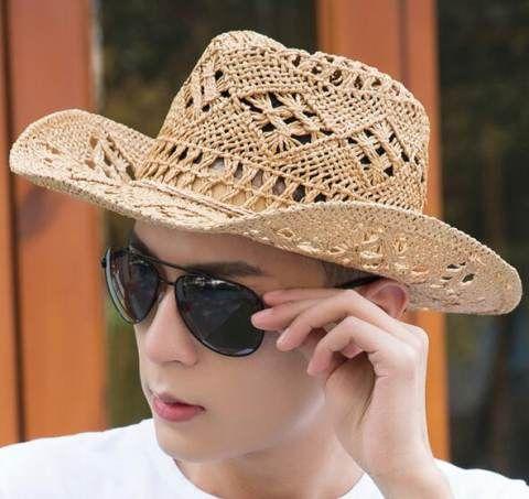 Jovem de óculos escuros e chapéu country de palha com detalhes que formam pequenos desenhos ao longo de sua extensão.