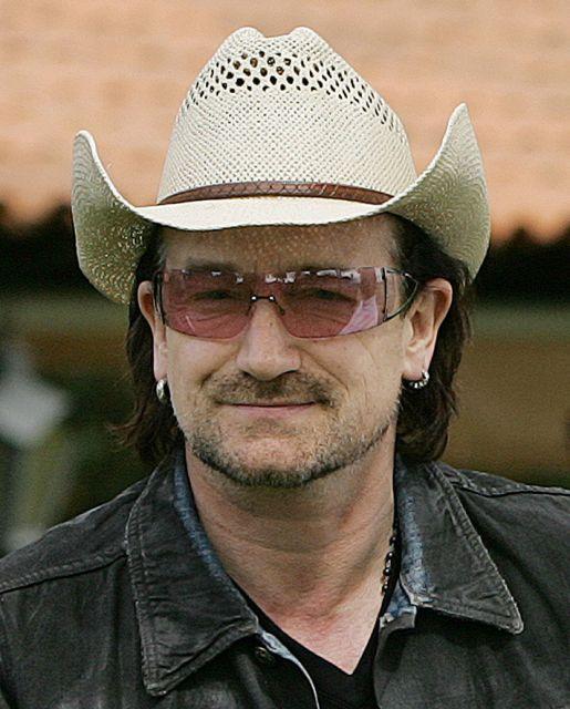 Bono Vox sorrindo enquanto usa seu típico chapéu de palha.