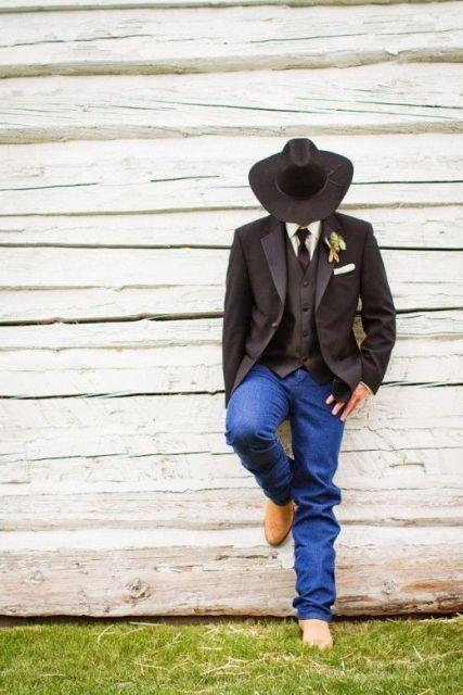 Homem recostado na parede de madeira. Ele usa bota, calça jeans, terno, colete, gravata e um chapéu country masculino preto.