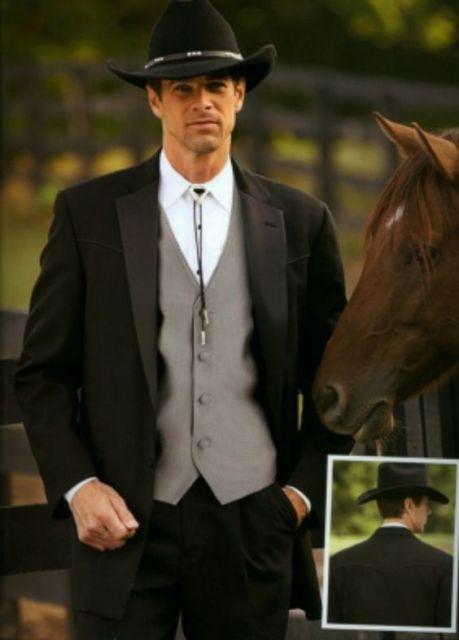 Homem de terno ao lado de um cavalo vestindo trajes sociais e um chapéu country com as coroa baixa.