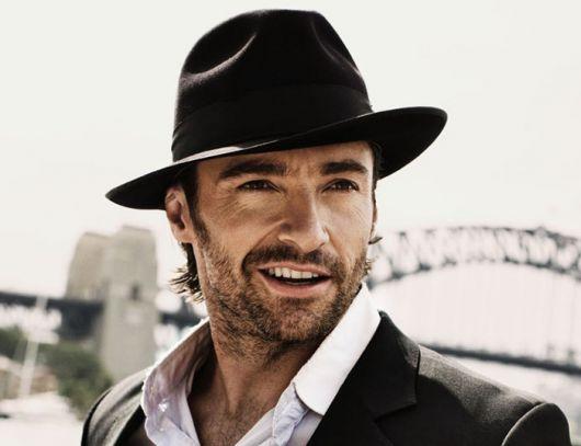 Modelo usa camisa branca, blazer e chapéu preto.