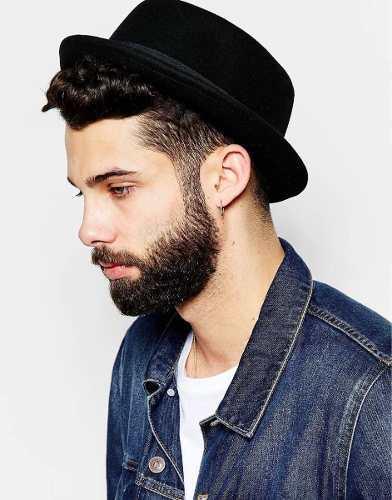Modelo usa camiseta branca, jaqueta jeans e chapéu fedora preto.