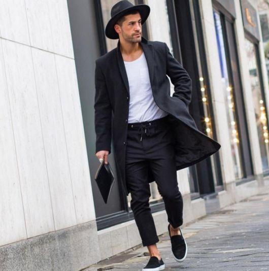 Modelo usa calça, casaco, sapato e chapéu fedora preto e camiseta branca.