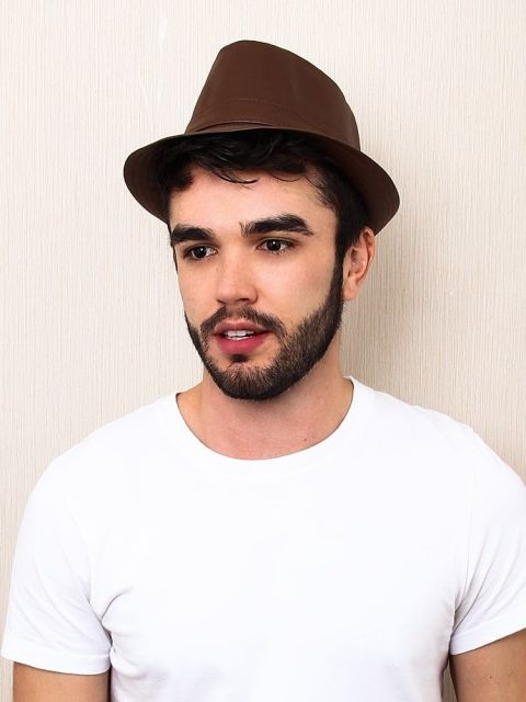 Modelo usa camiseta branca  e chapéu fedora marrom.