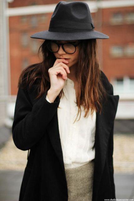 Modelo veste casaco preto, blusa branca e chapéu feminino.