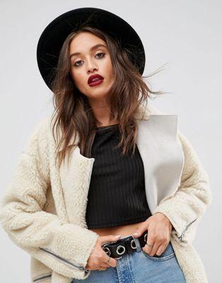 Modelo usa calça jeans azul, blusa preta, casaco  e chapéu fedora preto.