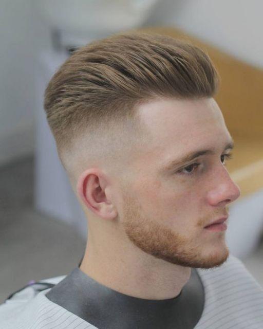 Homem na barbearia de perfil. Ele tem os fios do topo longos e penteados para trás, enquanto a lateral tem um degradê forte que começa alto e termina na máquina 0 até se unir à barba.
