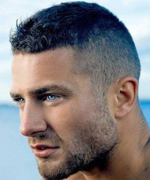 Foto tirada lateralmente de um homem com barba rala na mesma altura da lateral do cabelo. O topo é um pouco mais longo, mas ainda assim é curto.