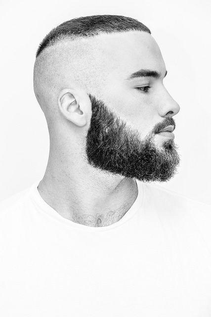 Homem de perfil com uma barba densa e bem desenhada. As laterais de sua cabeça são completamente raspadas e o topo é bastante curto, no estilo corte Caesar.