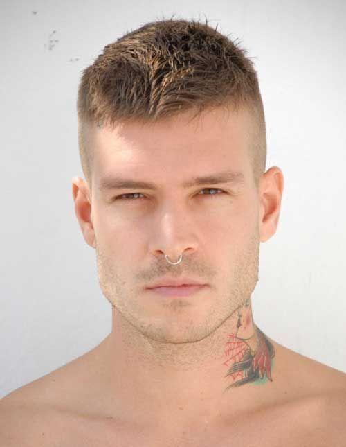Homem com pescoço tatuado e piercing no nariz olhando diretamente para câmera. As laterais de seu cabelo são raspadas e o topo é mais longo, levemente jogado para frente.