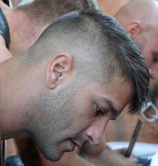 Homem de perfil com lateral da cabeça raspada e o topo mais alto, similar a uma moicano.