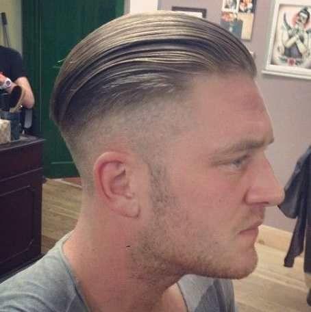 Homem de perfil com fade cut lateral e o topo com fios extensos penteados para trás com gel.