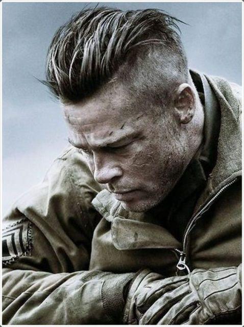 Brad Pitt no filme Corações de Ferro vestindo trajes do exército enquanto olha para baixo com expressão de preocupação. Seu cabelo é bem raspado nas lateral e o topo é mais longo, cortado em camadas e jogado para trás.