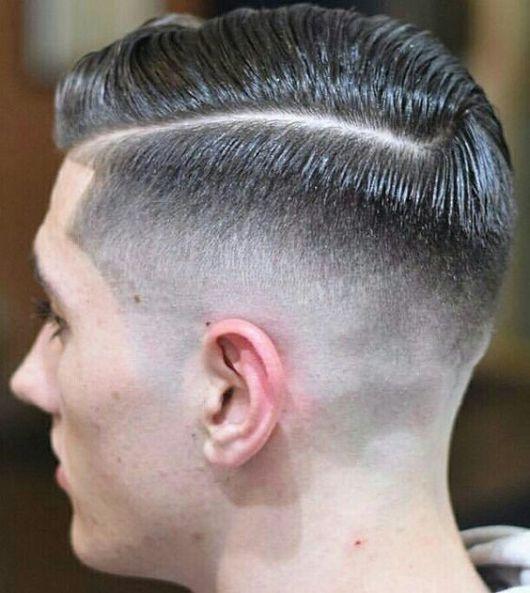 Homem de perfil com topete penteado para o lado e um risco na lateral marcando o início de um degradê.