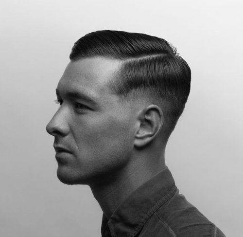 Homem de perfil usando o corte militar com uma risca básica na lateral que divide o topo e a lateral do cabelo.